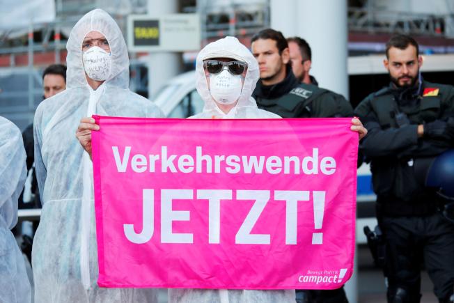 示威者15日堵住法蘭克福車展會場入口,抗議車商製造燃油車。一個蒙面抗議者拿著標語「回頭是岸!」。(路透)