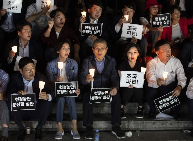 自由韓國黨黨魁黃教安(前排中)17日在首爾舉行燭光抗議活動,要求曹國辭。(歐新社)