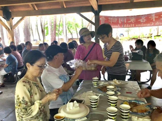 月餅製作主將莊惠瑾(立者右起)和李惠琴將客家綠豆椪發給參加者享用。(記者王明心/攝影)