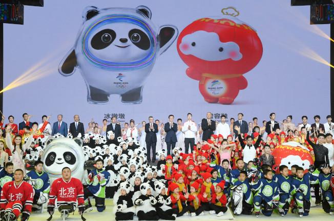 小朋友與北京2022年冬奧會吉祥物「冰墩墩」和冬殘奧會吉祥物「雪容融」合影。(新華社)