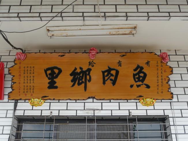 友人致贈的「魚肉鄉民」匾額別有意涵,要走近細看才會發現巧妙之處。(記者徐白櫻/攝影)