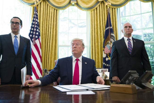川普今年6月24日簽署制裁伊朗的行政命令時,財長米努勤(左)與副總統潘斯(右)在場。美聯社
