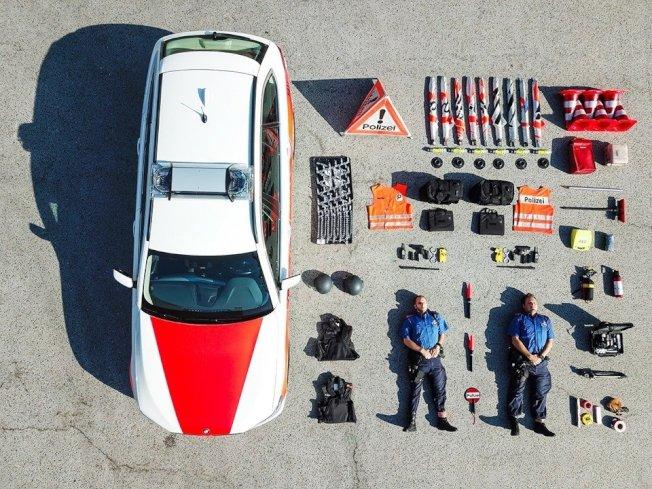 瑞士蘇黎世邦警察局月1日在臉書帳號發布一張空拍照,可見一輛警車、6個路錐、數十件警察隨身裝備和2名平躺警員整齊排列成方形。 圖/取自「Kantonspolizei Zürich - Kapo ZH」粉專