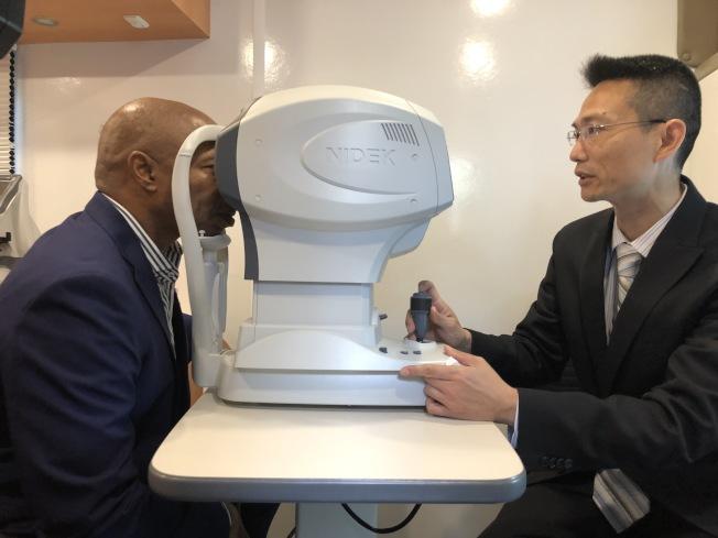 亞當斯(左)親臨醫療車接受眼科檢查服務。(記者顏潔恩/攝影)