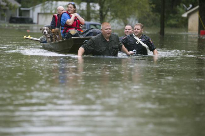 熱帶風暴伊美黛近日給德州和路易斯安那州部分地區帶來豪雨,部分市鎮三天降雨40吋。圖為德州警方用小船涉水護送災民至安全地方。(美聯社)