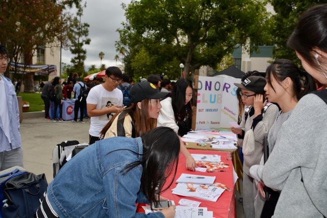 中國留學生在巴沙迪那社區學院資訊攤位前諮詢。(記者丁曙/攝影)