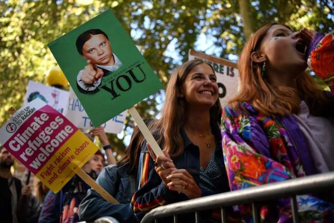 在英國倫敦,抗議氣候變遷活動的參與者舉起畫著環保小鬥士桑伯格(Greta Thunberg)的牌子。(Getty Images)