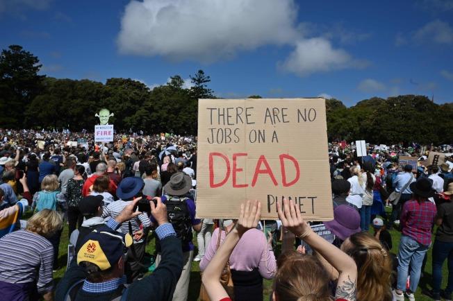 悉尼民眾參加抗議氣候變遷活動。圖中,一位民眾舉起寫著「滅亡了的星球上無工作」的標語。(Getty Images)