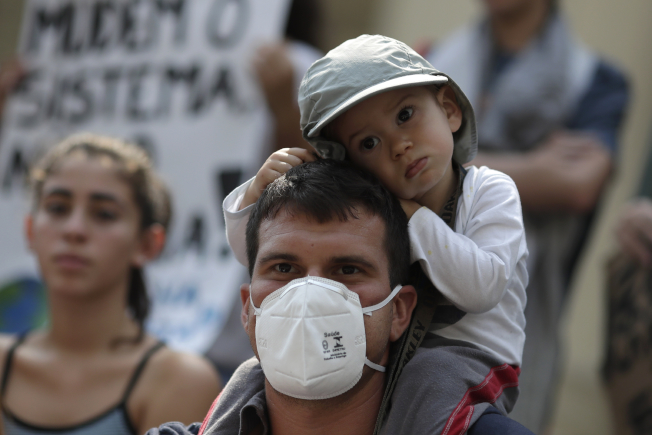 巴西里約熱內盧,一位父親帶著他的兒子參加氣候變遷抗議活動。(美聯社)