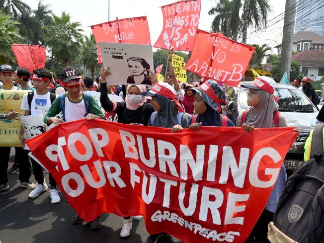 印尼學生舉著標語參加氣候變遷抗議活動。(Getty Images)