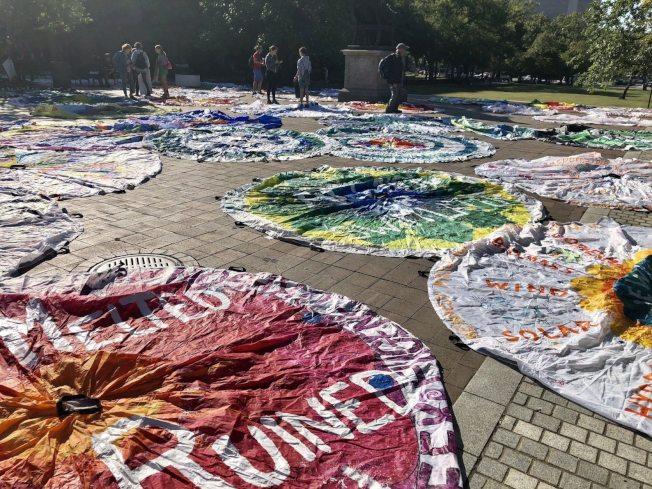 新聞博物館前的廣場鋪滿畫著環保圖案和標語的降落傘,抗議者用藝術表達環保理念。(取自WTOP)