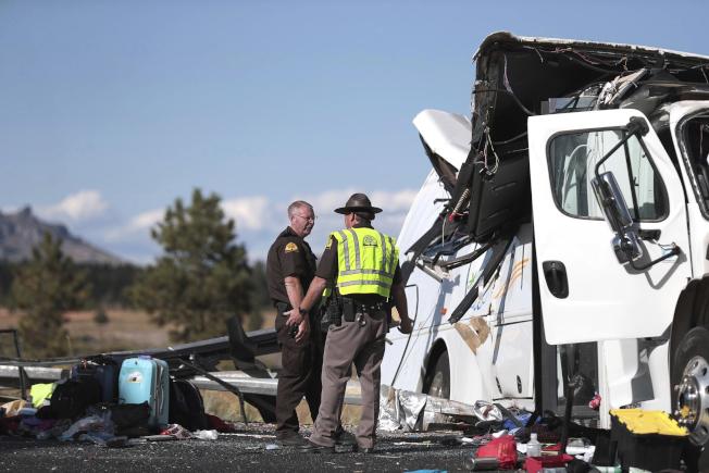 猶他州公路巡警站在變形的巴士前,旅遊團成員的行李散落一地。(美聯社)
