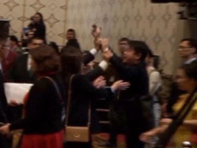 抗議者被工作人員包圍並帶出會場。(本報記者/攝影)