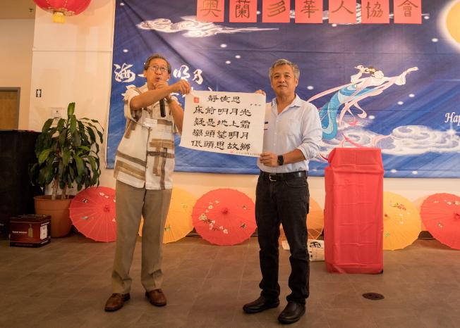 奧蘭多華人協會中秋聯歡會中,周國輝贈送親筆書法給前中國專協會長。(朱志凌提供)