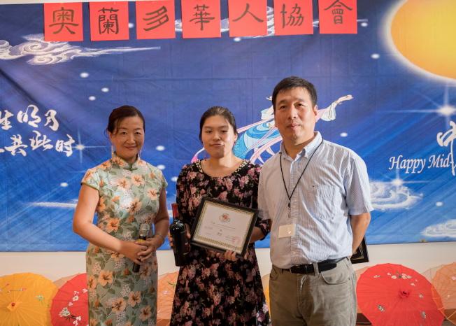 奧蘭多華會長邊發傑(右)為美食大賽第三名Amber(中)頒獎。左為薛蔚。(朱志凌提供)