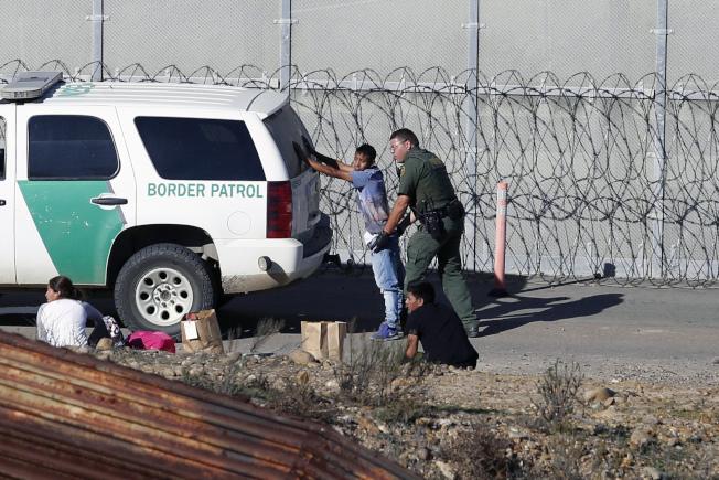 美國邊境巡邏隊員在加州聖地牙哥邊境攔下來自中美洲的無證移民。(美聯社)