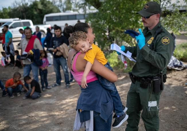 美國邊境巡邏隊員今年7月間在德州格蘭河邊遇到一對無證入境的薩爾瓦多母子,盤問並登記她的個人資訊。(Getty Images)