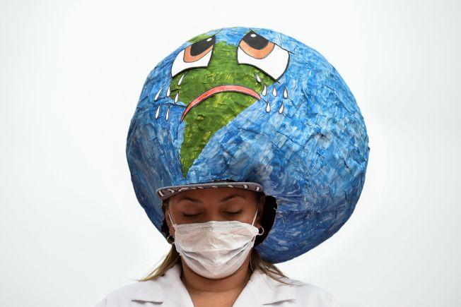 哥倫比亞一位女士戴著特殊的地球哭泣帽,響應全球抗議氣候變遷的行動。(Getty Images)