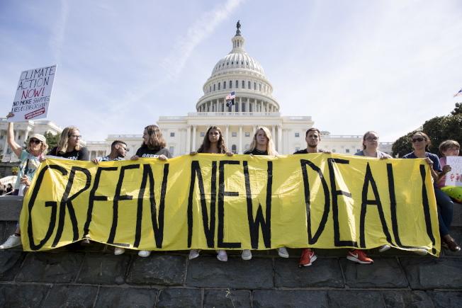 華府的青年示威者在國會前舉起橫幅要求「綠色新政」。(歐新社)