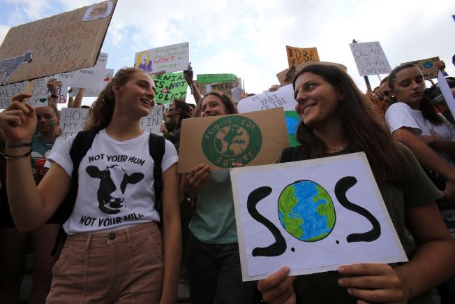 希臘青年走上雅典街頭,發出求救訊號,要求全球關注氣候變遷。(新華社)