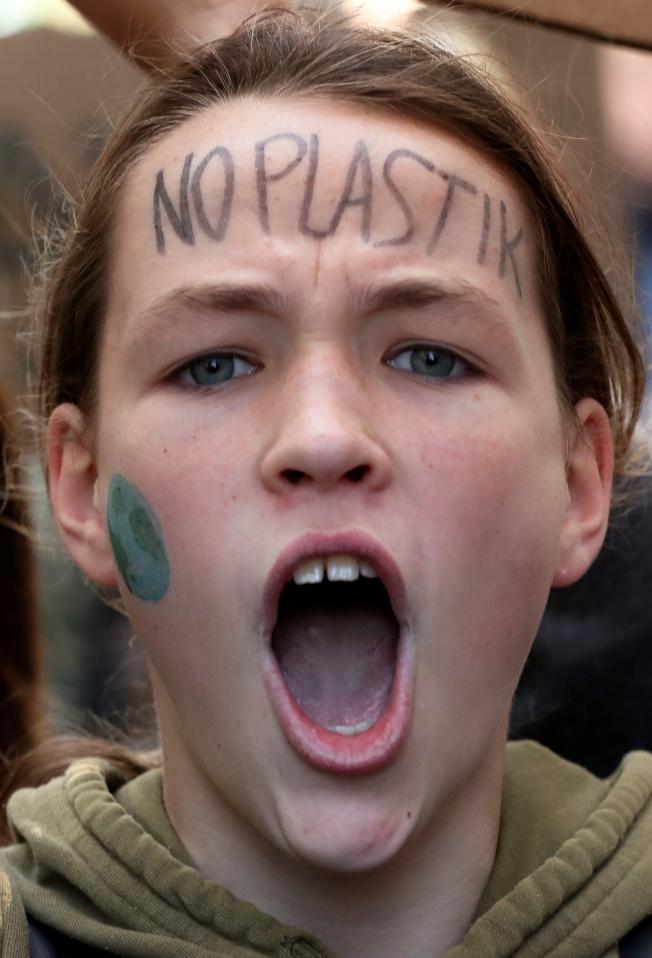 比利時學生上街示威,促全球關注環保,一名女學生額頭寫著「禁用塑膠」。(路透)