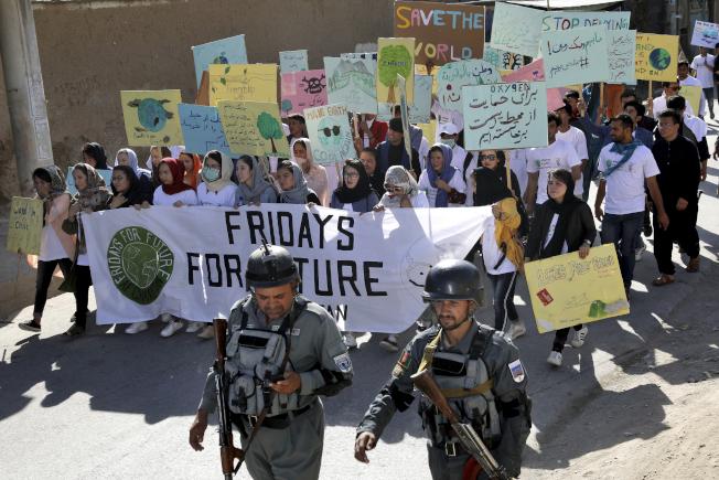 阿富汗青年響應全球對抗氣候變遷運動,在軍隊保護下上街示威。(美聯社)