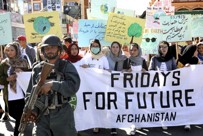 阿富汗青年在軍隊保護下,上街呼籲全球對抗氣候變遷。(美聯社)