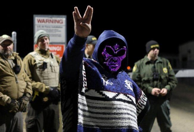 一名戴著外星人面具的「硬闖51區」參與者在美國內華達州極機密軍事基地「51區」大門外拍照。轟動一時的「硬闖51區,他們擋不了我們所有人」惡搞活動20日登場,超過2百萬人在臉書按下參加,最後只有約百人現身。路透