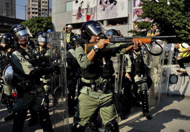 21日,一名香港警察將槍口對準示威群眾。美聯社