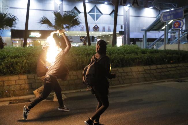 香港示威者向警方投擲自製汽油彈。(美聯社)