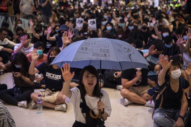 元朗白衣人襲擊事件滿兩個月,21日晚間一批香港市民到元朗一商場內靜坐示威,高唱「願榮光歸香港」,高呼「五大訴求,缺一不可」等口號。(歐新社)