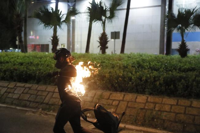 香港示威者向警方投擲自製汽油彈,卻引火燒身。(美聯社)