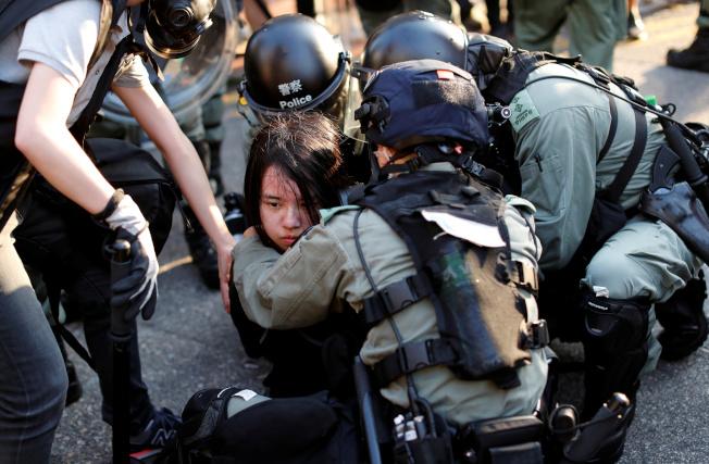香港民眾21日舉行「光復屯門」遊行,警民再爆衝突,圖為警方拘捕一位參與遊行的示威者。(路透)