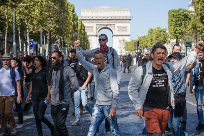 法國黃背心示威者參加對抗暖化示威,走在巴黎香榭麗舍大道喊口號。(新華社)