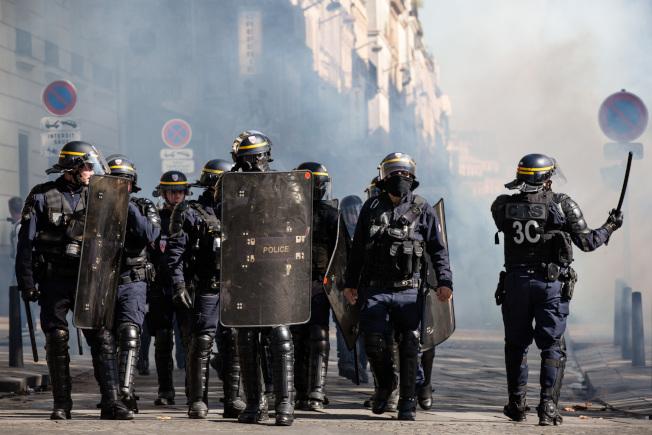 對抗氣候暖化的示威變質,黃背心重上巴黎街頭,鎮暴警察在香榭麗舍大道驅逐示威者。(新華社)