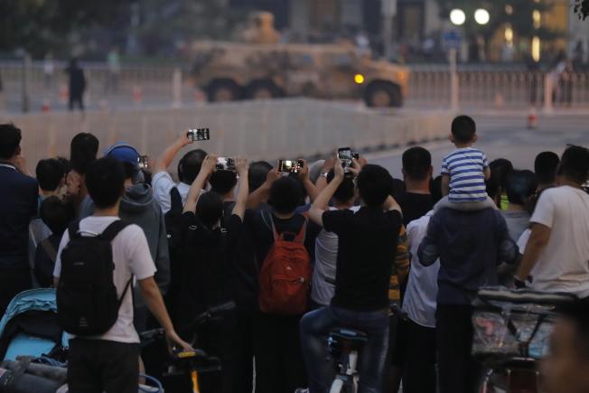民眾圍觀為國慶閱兵綵排通行的軍車。(歐新社)