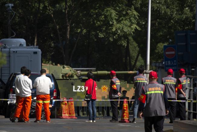 北京昨天起進行「十一」活動的第三次預演,許多路段都禁行,停放在街邊的裝甲車,吸引民眾注目,包括穿著「朝陽群眾」字樣衣服的維安人員。(美聯社)