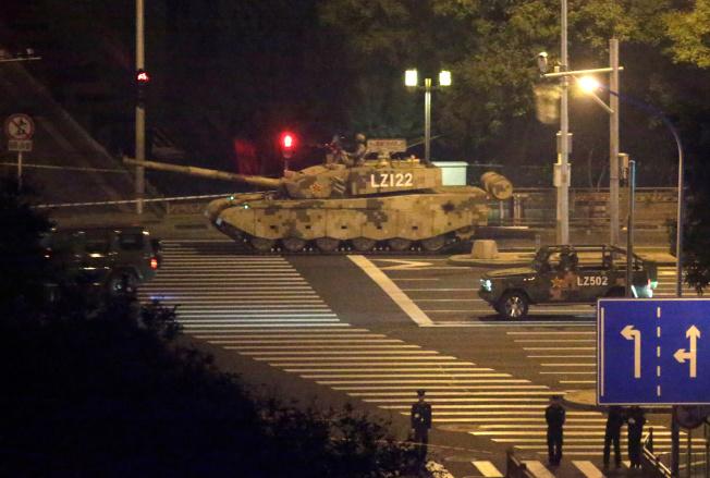 一輛坦克自北京封閉的街道通過。(路透)