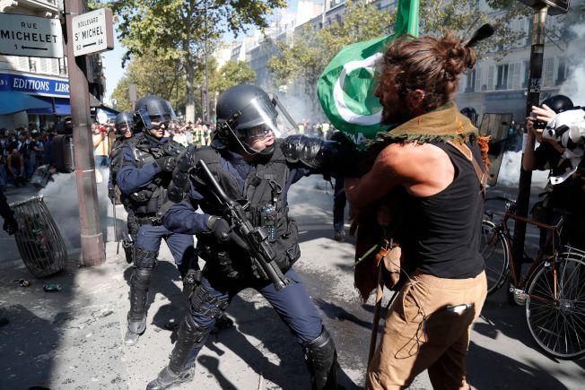 對抗氣候暖化的示威變質,演變成示威者與警察的對抗,圖為一名示威者與鎮暴警察發生衝突。(Getty Images)