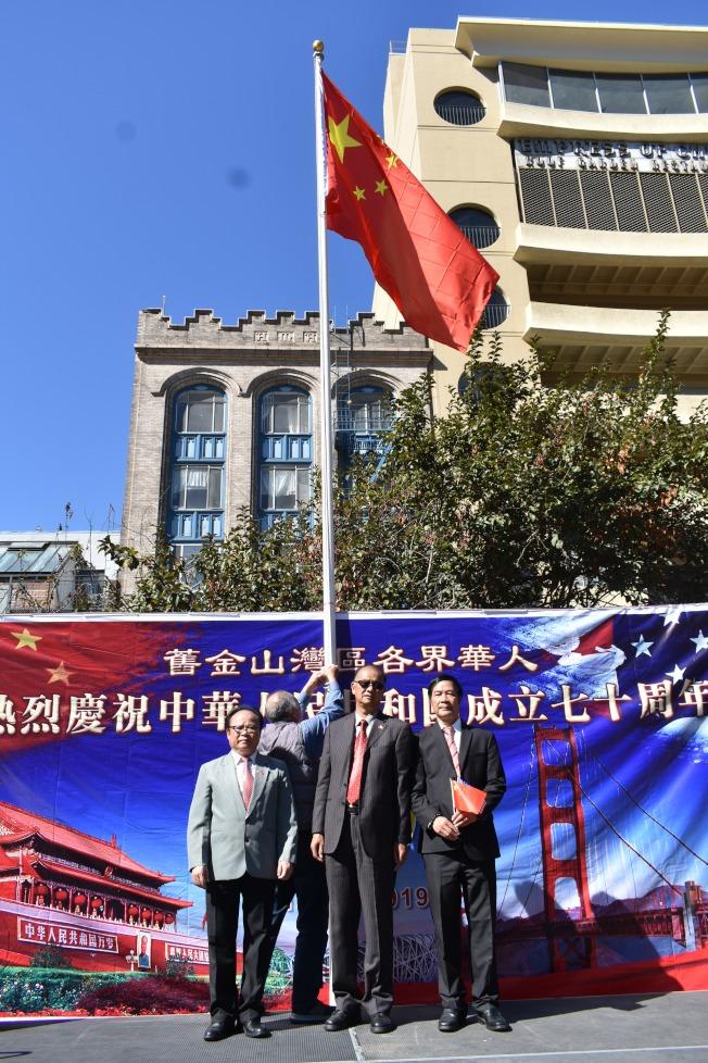 執行主席張福明(中)、黃楚文(右)、何偉明(左)在華埠花園角廣場升起五星紅旗。(記者黃少華/攝影)