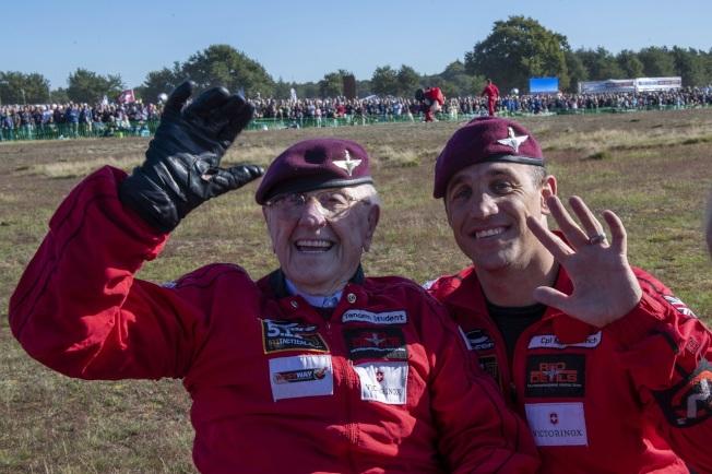 今年已97歲的英國老兵寇特曼(左)21日與英國陸軍「紅魔鬼」(Red Devils)跳傘表演小組一位成員在荷蘭安恆的Ginkel Heath降落區合影。(美聯社)
