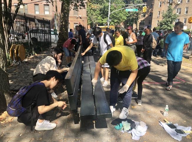 學生義工們為楓林運動場的椅凳粉刷油漆。(記者朱蕾╱攝影)