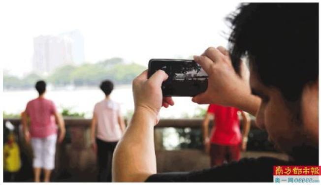 非視覺攝影師龍井在珠江邊創作。(取材自南方都市報)