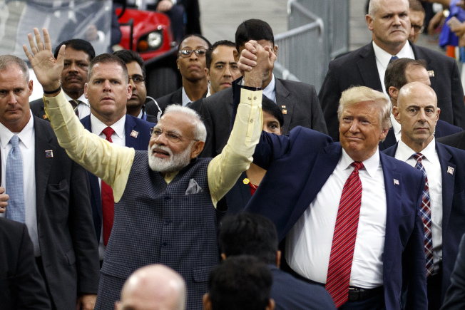 休士頓22日舉行歡迎印度總理莫迪的盛大集會。圖為川普總統(右)和莫迪攜手步入會場。(美聯社)