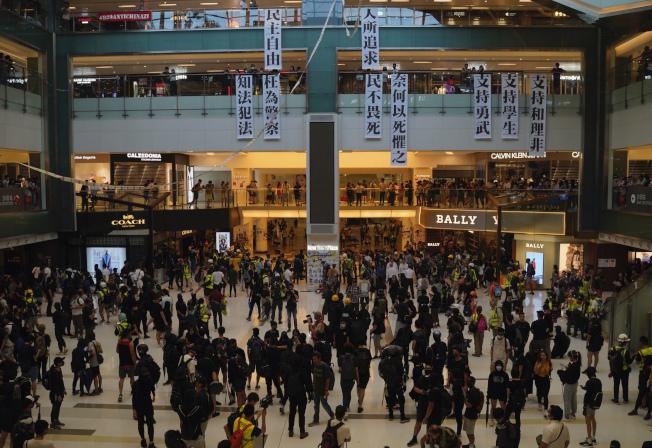 大批反送中示威者22日再次發起抗爭活動,他們進入購物中心,掛起追求民主自由、支持學生的標語,要求港府接受示威者提出的訴求。(美聯社)