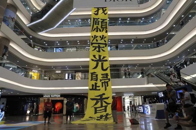 大批反送中示威者22日再次發起抗爭活動,他們進入購物中心,掛起追求民主自由、支持學生的標語。(美聯社)