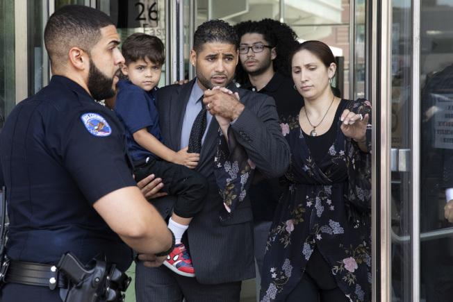 羅德格斯(左三)在案發後,懷抱兒子,在妻子陪同下出庭。(美聯社)