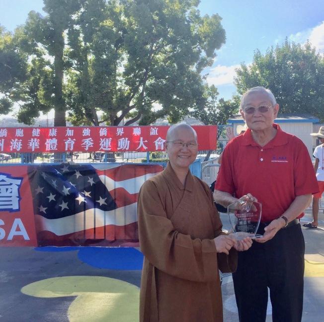 佛光山西來寺中文學校獲學童男子組第二名,美國中華體育聯誼會會長高啟正(右)向西來寺師父頒贈獎牌。(美國中華體育聯誼會提供)