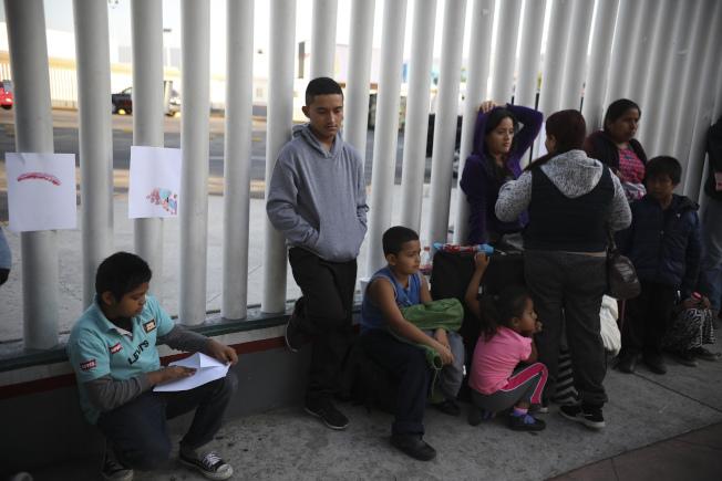 全美各地移民法庭累積未消化的無證移民申請庇護案件在今年8月超過了100萬件,較2017年1月初總統上任時,幾乎多出一倍。圖為打算申請庇護的移民在美墨邊界等候叫號。(美聯社)