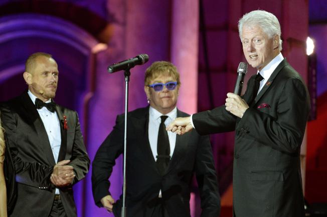 前總統柯林頓(右)2013年在維也納演講時,介紹身旁的艾爾頓強(中)。(美聯社)